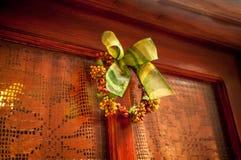 用传统圣诞节弓装饰的木门照片 免版税库存图片