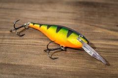 用作鱼饵的微曲金属片,诱剂,飞行,抓或钓鱼的一条掠食性鱼滑车在甲板木头背景 免版税库存照片