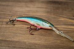 用作鱼饵的微曲金属片,诱剂,飞行,抓或钓鱼的一条掠食性鱼滑车在甲板木头背景 库存图片