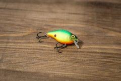 用作鱼饵的微曲金属片,诱剂,飞行,抓或钓鱼的一条掠食性鱼滑车在甲板木头背景 免版税图库摄影