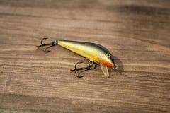 用作鱼饵的微曲金属片,诱剂,飞行,抓或钓鱼的一条掠食性鱼滑车在甲板木头背景 图库摄影