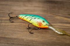 用作鱼饵的微曲金属片,诱剂,飞行,抓或钓鱼的一条掠食性鱼滑车在甲板木头背景 库存照片