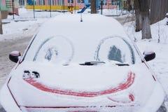 用冰和雪盖的冻汽车挡风玻璃在一个冬日 微笑 免版税库存照片