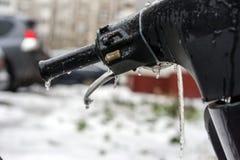用冰盖的摩托车把柄在冻雨以后 免版税库存图片