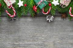 用冷杉分支、装饰、礼物盒和杉木锥体做的圣诞节或新年快乐背景在木桌 免版税库存照片