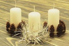 用冷杉球果和银色闪亮金属片装饰的三个白色蜡蜡烛在黑暗的木背景 库存照片
