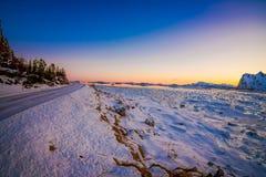 用冻湖雪和海边报道的路室外看法惊人的日落的在北极圈的冬天 库存照片