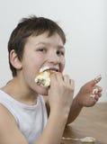 用力嚼在一个奶油色小圆面包 免版税库存照片