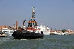 用力拖小船从口岸提出游轮 免版税库存照片