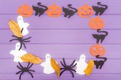 用南瓜、猫、鬼魂和蜘蛛不同的纸剪影的万圣夜圆的框架与秋叶 免版税库存照片