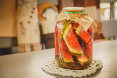 用卤汁泡的或烂醉如泥的西瓜用在一个玻璃瓶子的草本在一张木桌上在厨房里 免版税库存图片