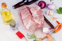 用卤汁泡的新鲜的未加工的猪排、橄榄油、辣椒、红洋葱和绿色在木背景 免版税图库摄影