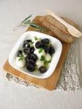 用卤汁泡的无盐干酪用黑橄榄、橄榄油和芥末叶子 库存照片