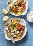 用卤汁泡的酸奶烤了鸡胸脯和以色列蒸丸子和菜tabouli沙拉在蓝色背景 免版税库存照片