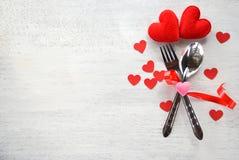 用叉子匙子和红心装饰的华伦泰晚餐浪漫爱概念浪漫桌设置在白色木 免版税库存图片