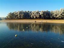 用发光,稀薄的冰层数盖的消遣湖 免版税库存图片