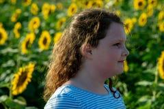 用向日葵享受自然和笑在夏天向日葵领域的秀丽快乐的女孩 Sunflare,光束,焕发 免版税库存图片