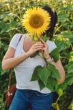 用向日葵盖的妇女面孔 库存照片