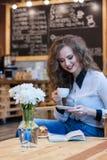 用咖啡读书的美丽的女孩 免版税库存照片