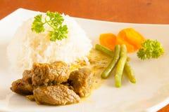 用咖喱粉烹调的山羊服务用白米,菜豆并且切了红萝卜 库存照片