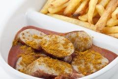 用咖喱粉烹调的炸薯条香肠 免版税图库摄影