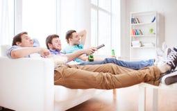 用啤酒在家看电视的愉快的男性朋友 库存照片