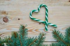 用圣诞树装饰的绿色糖果锥体的心脏在棕色木背景分支 新年或情人节食物 库存图片