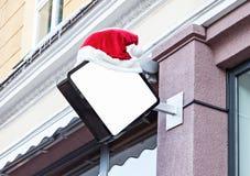 用圣诞老人帽子装饰的公司标志在圣诞节期间 库存照片