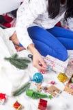 用圣诞节礼物盒装饰的一件舒适编织毛线衣的女孩 库存照片