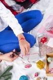用圣诞节礼物盒装饰的一件舒适编织毛线衣的女孩 免版税库存图片