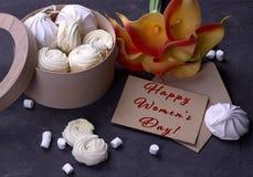 用在一个木圆的箱子的蛋白软糖在灰色木背景在愉快的妇女` s天英语上写字的绿色黄色水芋属花束  图库摄影