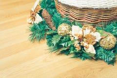 用在一个柳条筐的一中央装饰的圣诞节装饰品在黄色硬木地板上 免版税库存照片