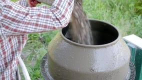 用在一台混凝土搅拌机的石渣盖的工作者的手用桶提 具体倾吐 混合沙子,石渣和 股票录像