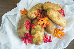 用在一块白色布料的秋叶盖的静物画土豆 免版税库存图片