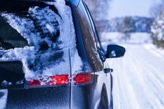 用在一条危险路的雪盖的汽车。 免版税库存图片