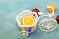 用在一辆装饰自行车的切的柠檬用在蓝色背景带来的果子 免版税库存图片