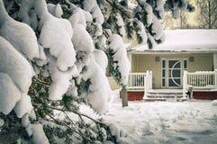 用在乡下房子前面的雪报道的云杉的分支在1月 库存照片