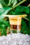 用在冰的梨切片装饰的层状黄色射击鸡尾酒 查出在绿色背景 免版税库存图片