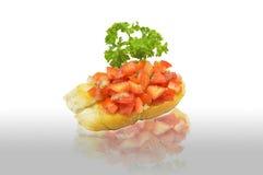 用在地板反射的荷兰芹叶子装饰的蕃茄bruschetta在白色背景 库存照片