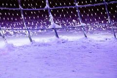 用在夜st的多盏圣诞灯装饰的斯诺伊框架 图库摄影