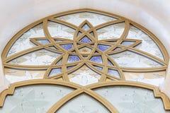 用在扎耶德与蓝天的Grand Mosque回教族长的金黄几何形式装饰的玻璃窗早晨在阿布扎比,阿拉伯联合酋长国 免版税库存图片