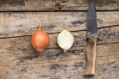 用在木背景的刀子整个和切成两半的葱 免版税图库摄影