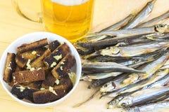用在杯子的大蒜油煎方型小面包片啤酒和干鱼旁边 免版税库存照片