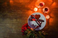 用在板材和夫妇香槟玻璃酒的叉子匙子装饰的华伦泰晚餐浪漫爱conceptRomantic桌设置 免版税库存图片