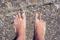 用在海滩的沙子包括的妇女` s赤脚 免版税库存照片