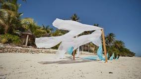 用在海滩的花装饰的婚礼曲拱在海洋附近 她的白色和蓝色帆布在风飞行 装饰 影视素材
