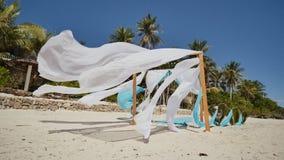 用在海滩的花装饰的婚礼曲拱在海洋附近 她的白色和蓝色帆布在风飞行 装饰 股票视频