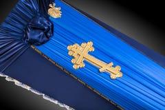 用在灰色背景的布料盖的被关闭的蓝色棺材 与金教会十字架的棺材特写镜头 免版税图库摄影