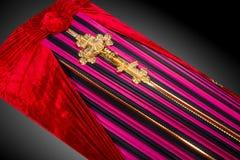 用在灰色背景的布料盖的闭合的桃红色棺材 与金教会十字架的棺材特写镜头 免版税库存照片