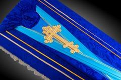 用在灰色背景的布料盖的闭合的蓝色棺材 与金教会十字架的棺材特写镜头 库存照片